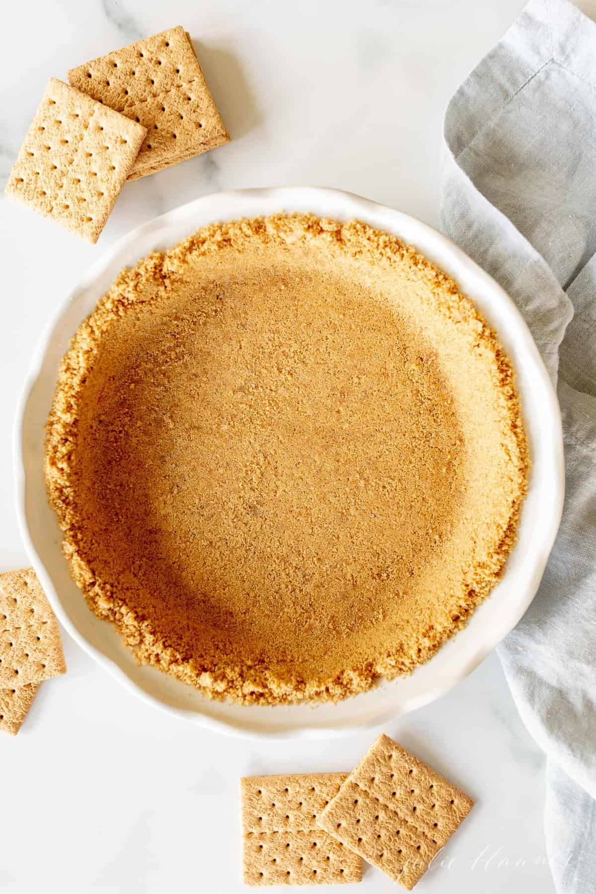 graham cracker crust in white dish with blue napkin