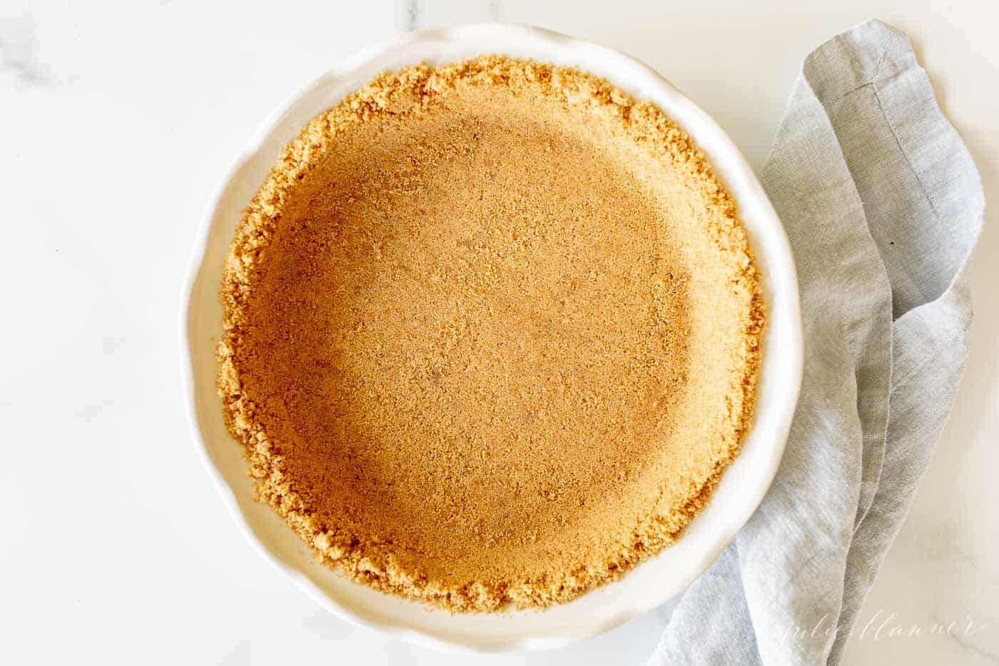 graham cracker pie crust in white dish with blue napkin