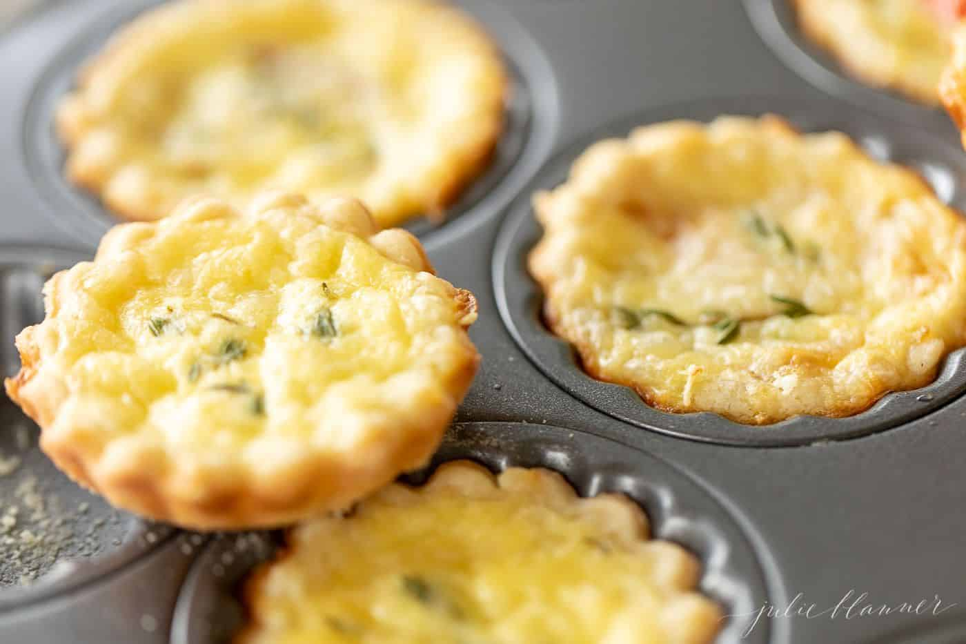 A metal tart pan with small cheese tarts with an easy pie crust recipe as the scalloped edges.