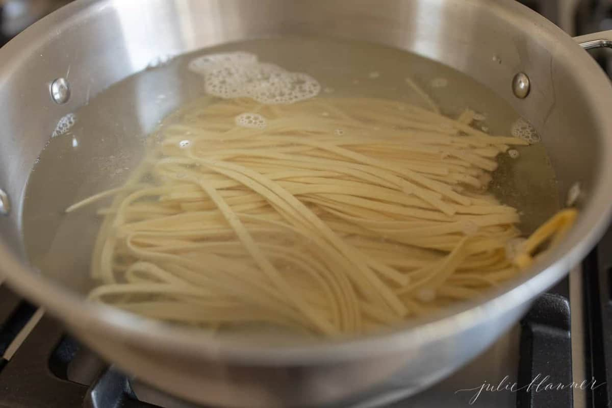 A silver pan filled with water and fettuccine