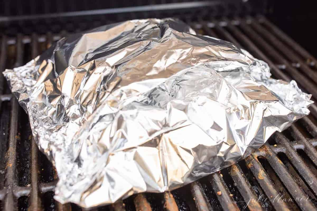 A chunk of aluminum foil on a grill, baked salmon with lemon inside.
