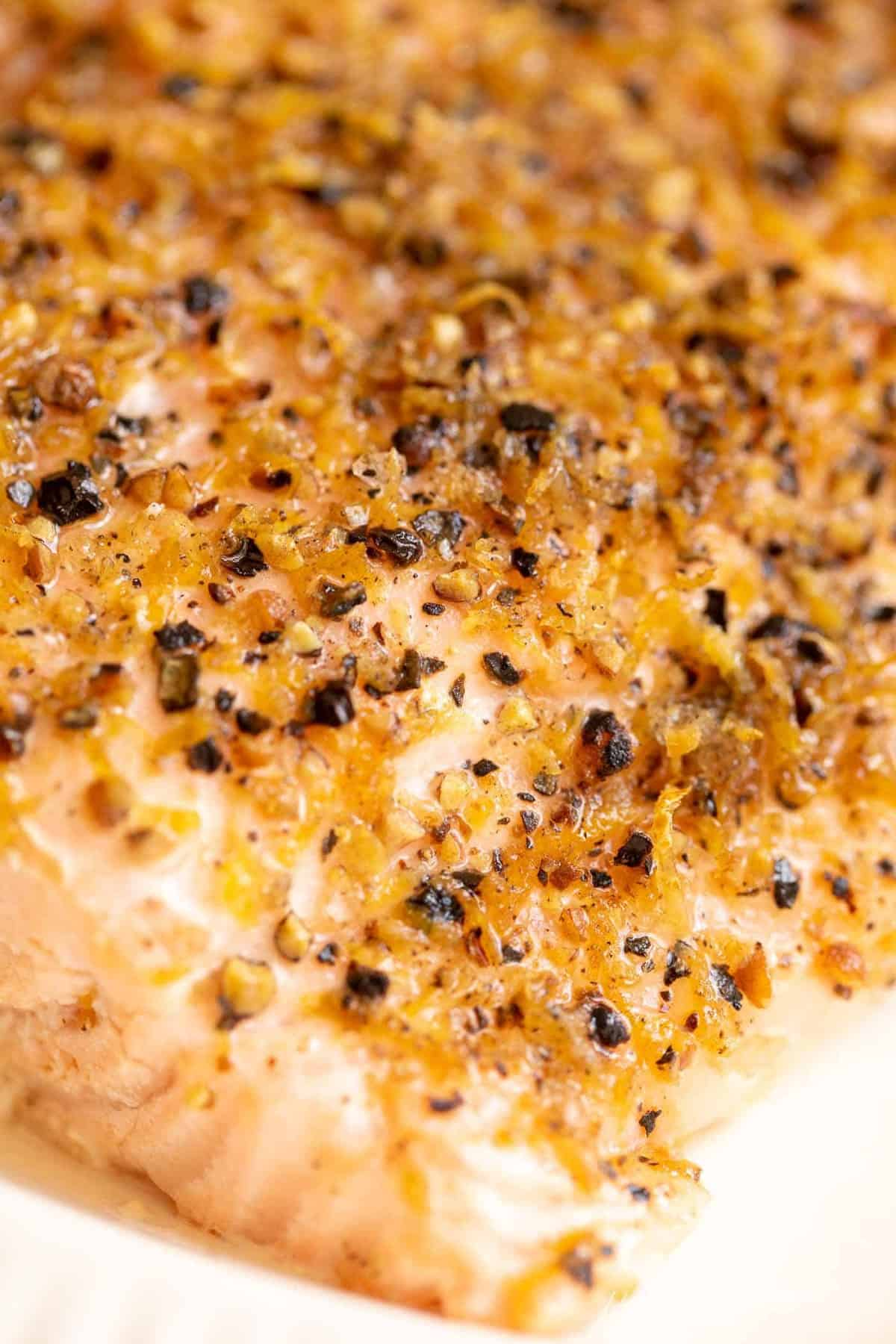 A close up shot of a fillet of lemon pepper salmon recipe.