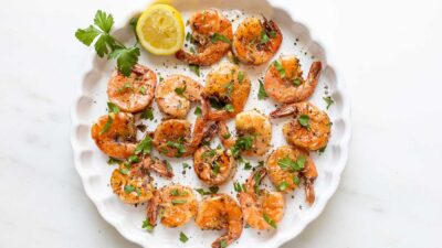 A round plate full of cooked lemon pepper shrimp.
