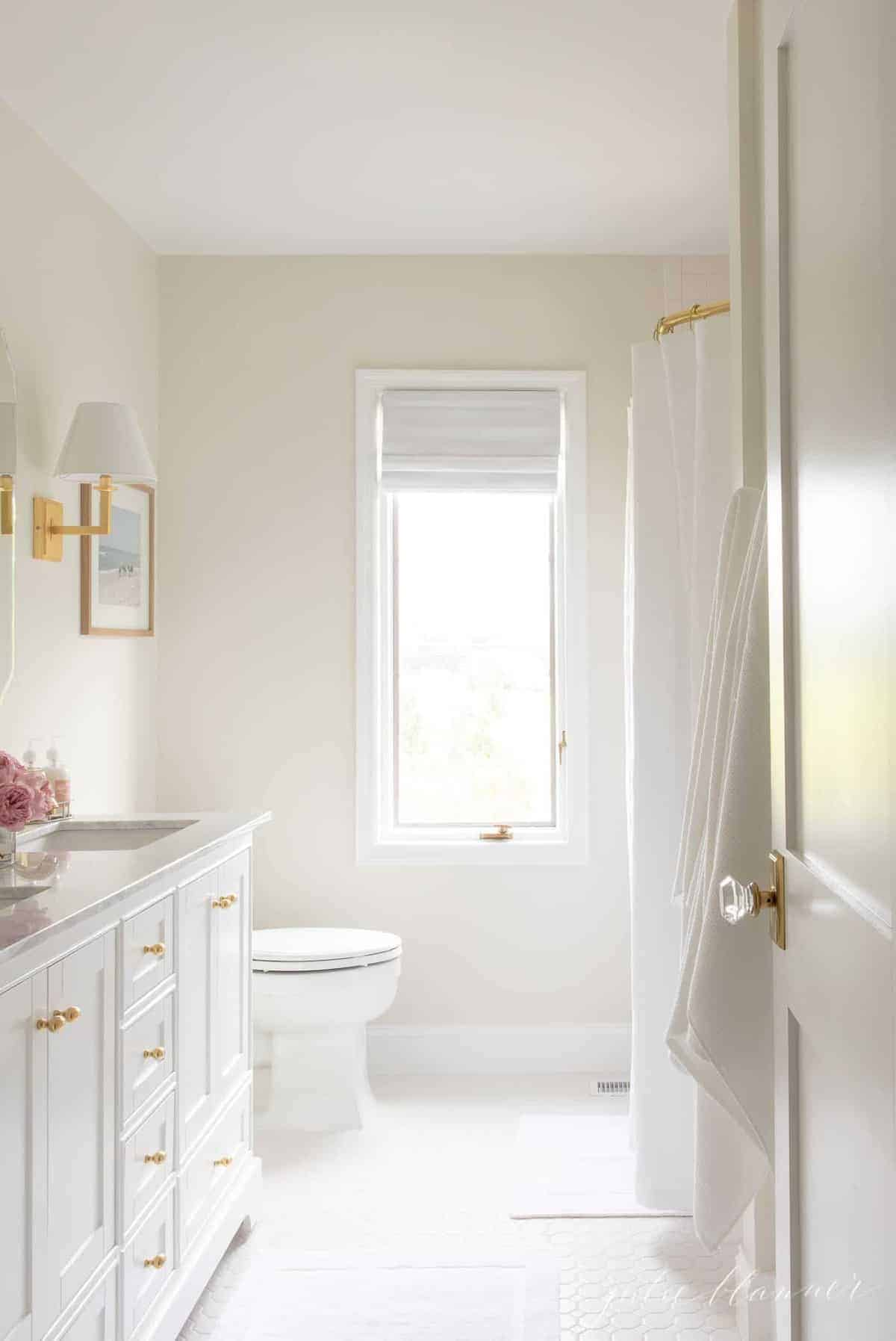 A white bathroom with gold hardware.