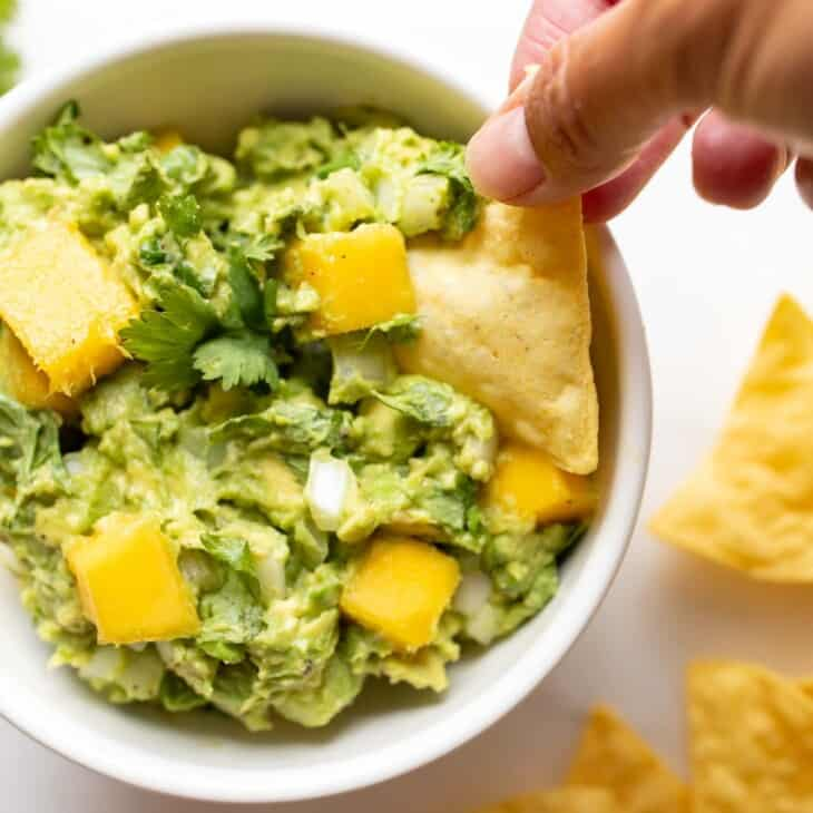 A white bowl on a marble surface full of mango guacamole, chips to the side and a hand reaching into the dip bowl.