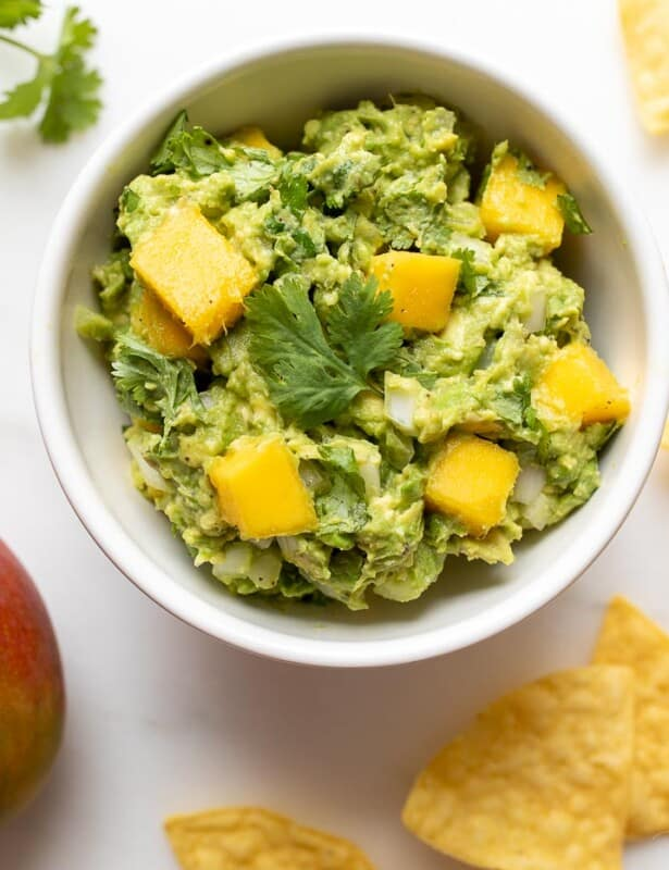 A bowl of mango guacamole and its ingredients around it