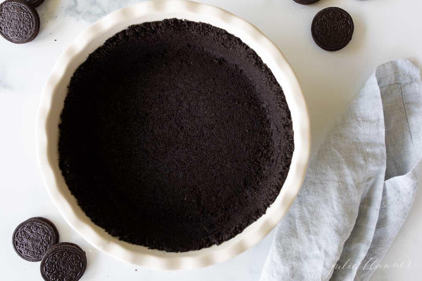 Um prato de torta de cerâmica branca com uma receita de crosta oreo dentro, oreos ao lado.
