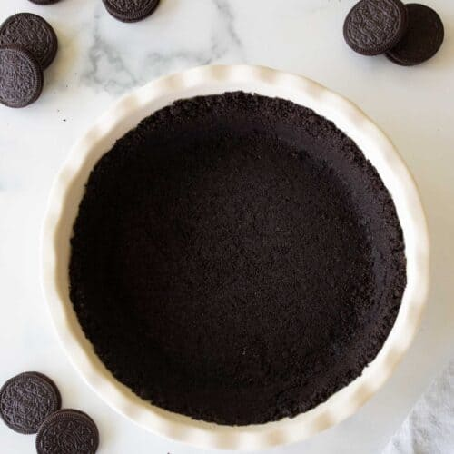 A white ceramic pie dish with an oreo crust recipe inside, oreos to the side.