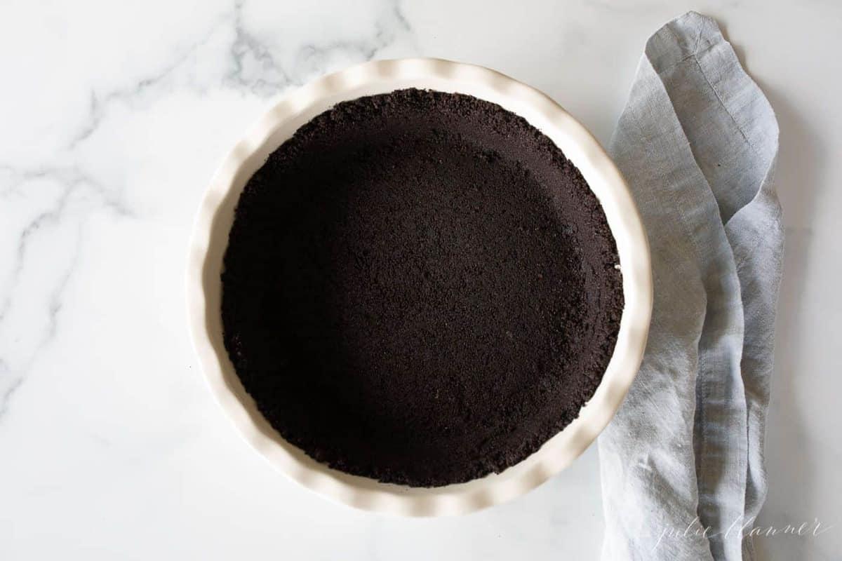 Uma forma de torta de cerâmica branca com uma crosta de biscoito de oreo dentro, toalha de linho azul ao lado.