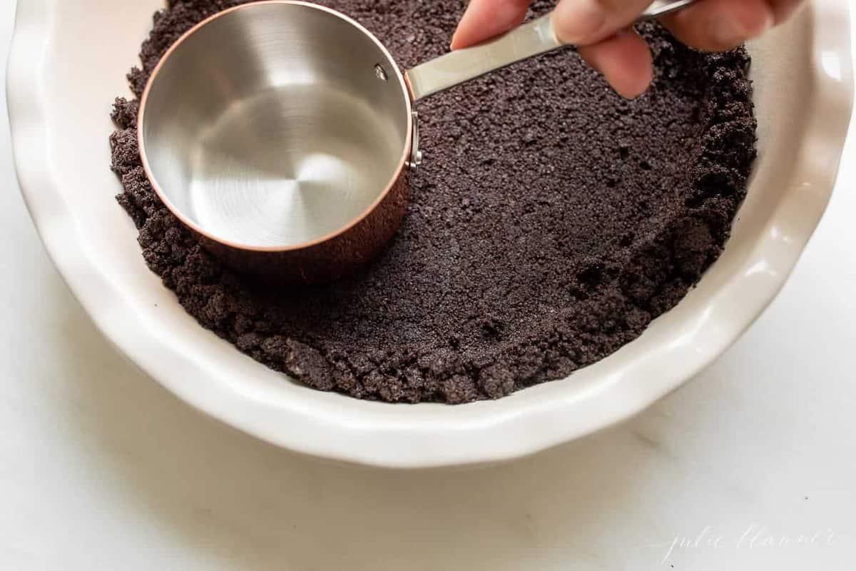 Uma mão pressionando migalhas de biscoito oreo em uma forma de torta com um copo medidor para uma crosta de biscoito oreo.
