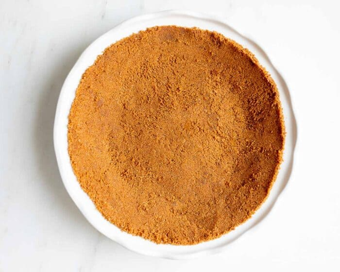 A white pie pan full of speculoos cookie crust for a pie.