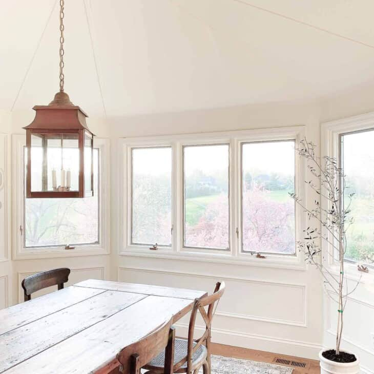 A white dining room with modern light fixtures and a big window.