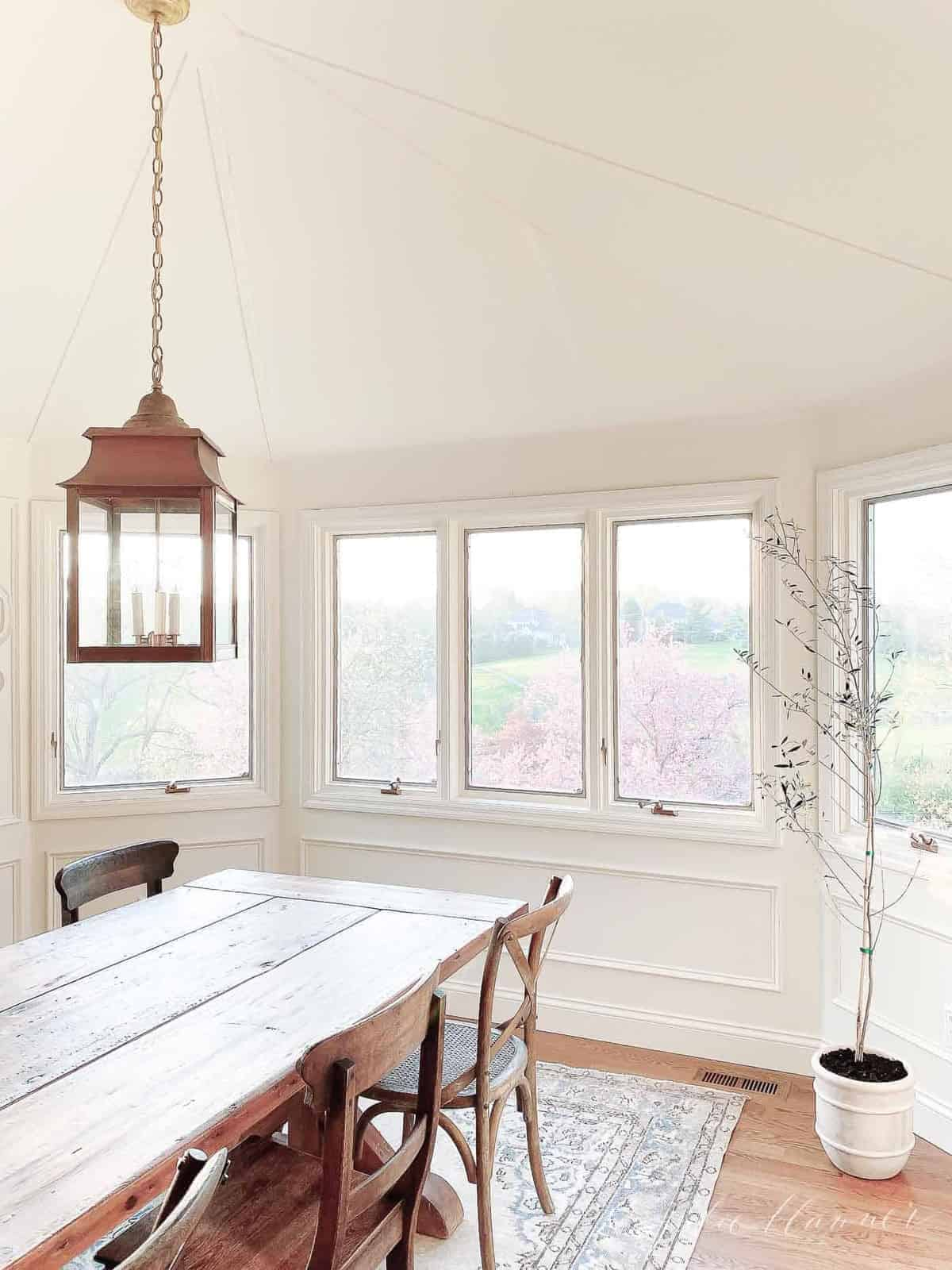A white dining room with a farm table and a brass lantern above.