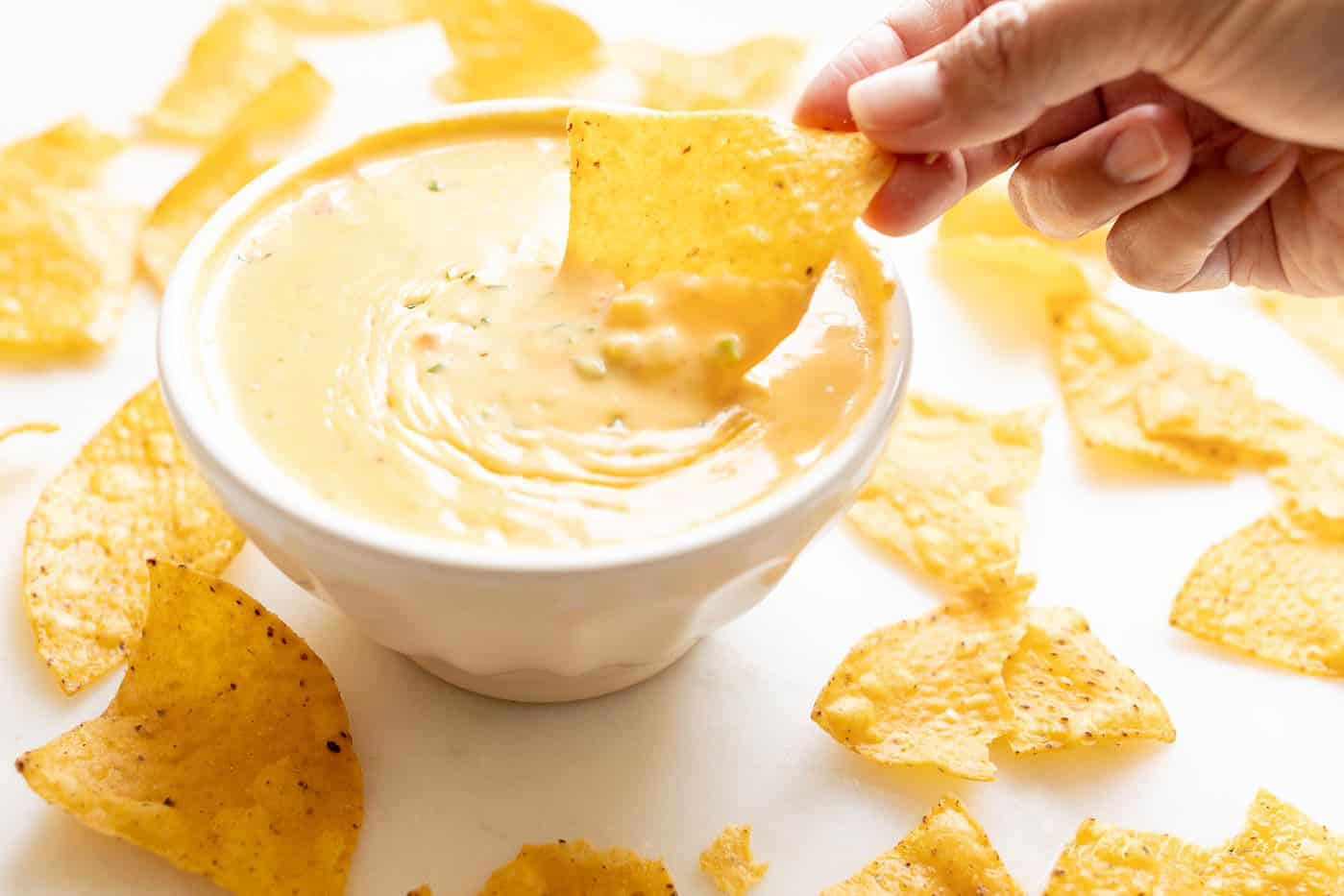 A hand reaching into a bowl full of Velveeta cheese dip, chips surrounding the bowl.