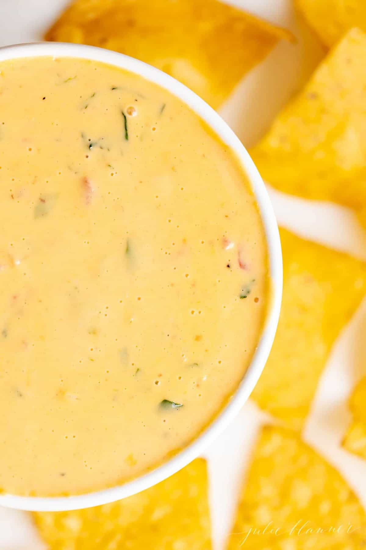 A white bowl full of cheese dip surrounded by tortilla chips.