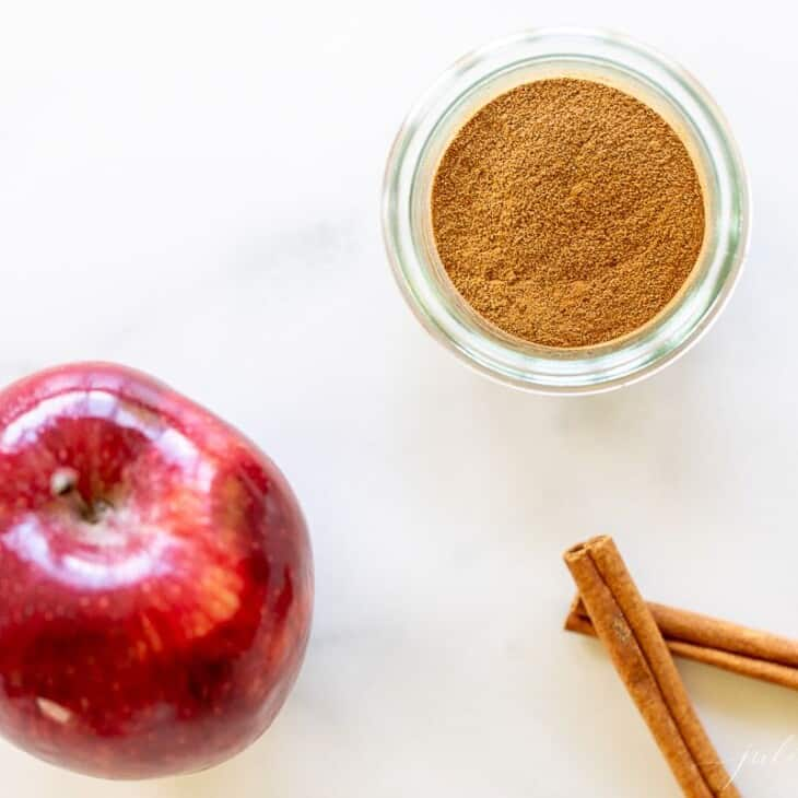 A marble surface with a small jar of apple pie spice, cinnamon sticks and an apple to the side.