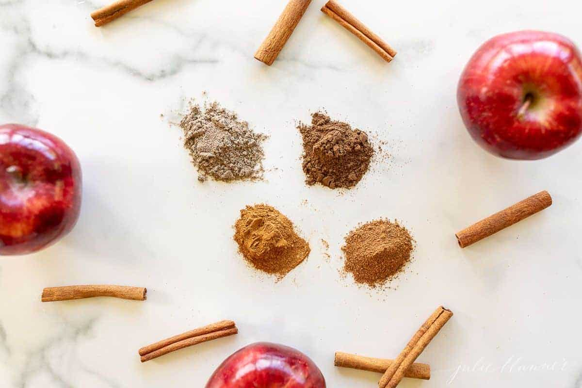 A marble surface filled with seasoning piles, cinnamon sticks and apples to make an apple pie spice recipe.