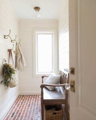 A white shiplap mudroom with thin brick flooring, brass hooks on the walls and a wooden bench.