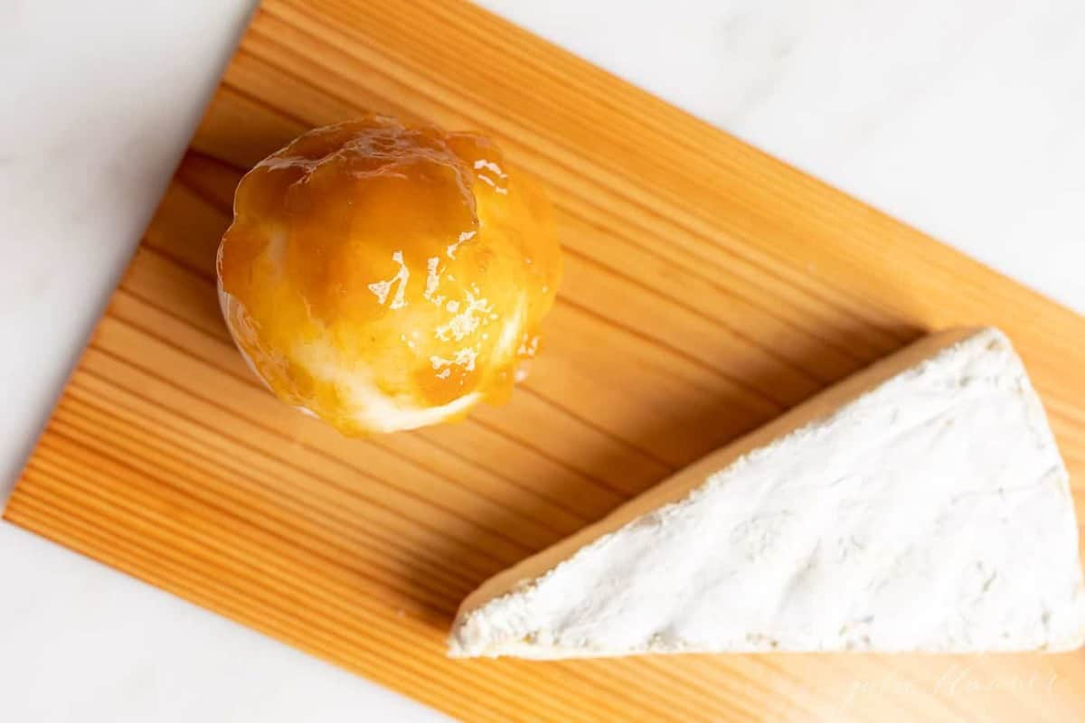 A wedge of brie and a ball of mozzarella on a cedar plank