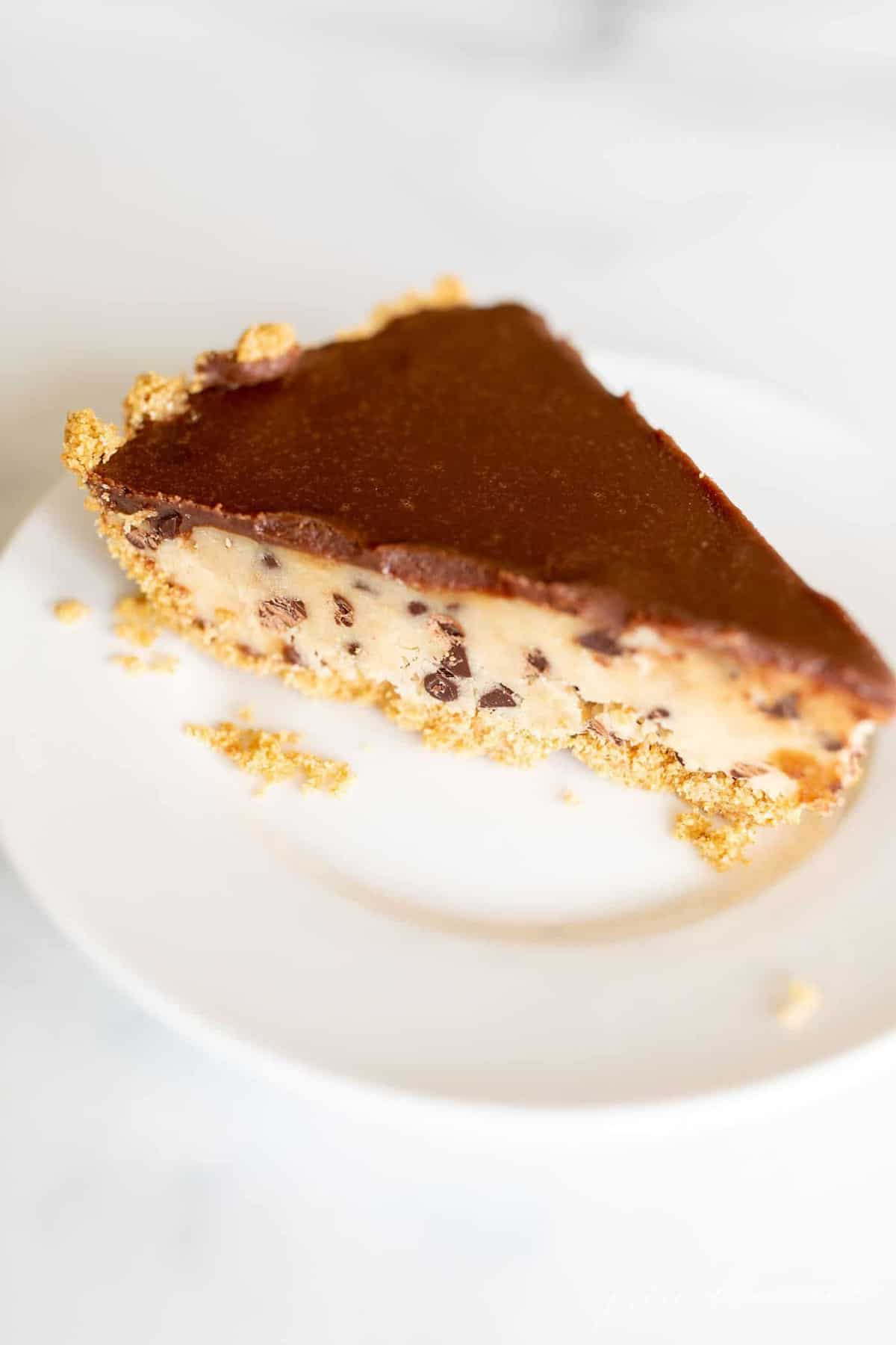 A slice of no bake cookie dough pie on a white plate.