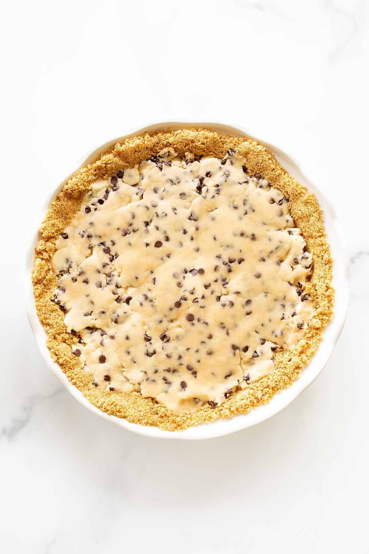 Cookie dough pie filling inside a homemade pie crust on a marble surface.