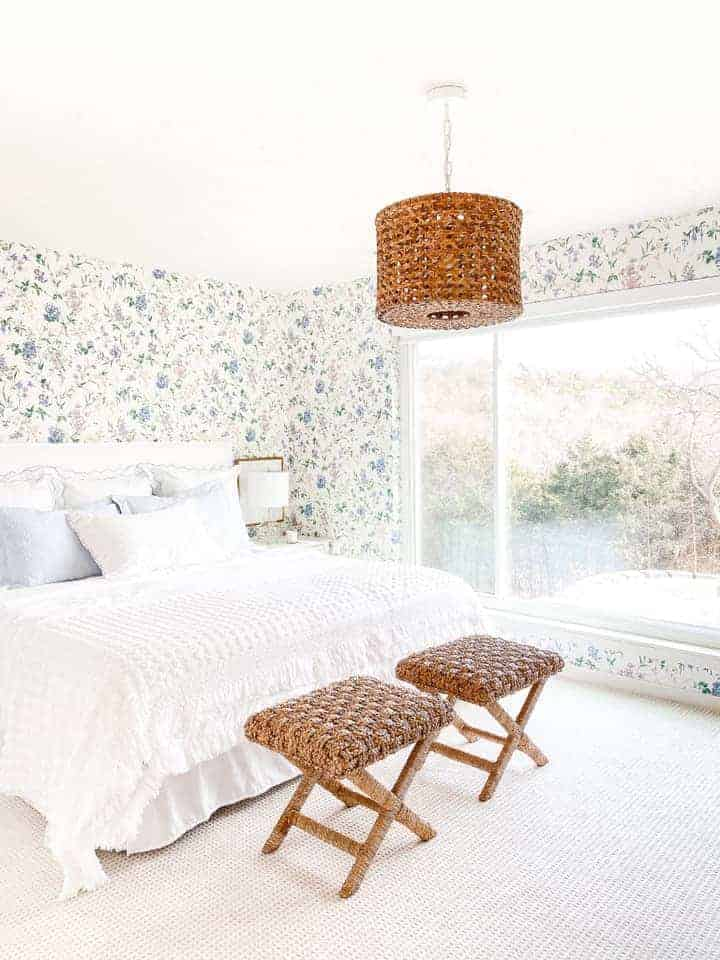A bedroom with patterned floral slightly dated wallpaper, updated with fresh white bedding and pretty textures with a large window.