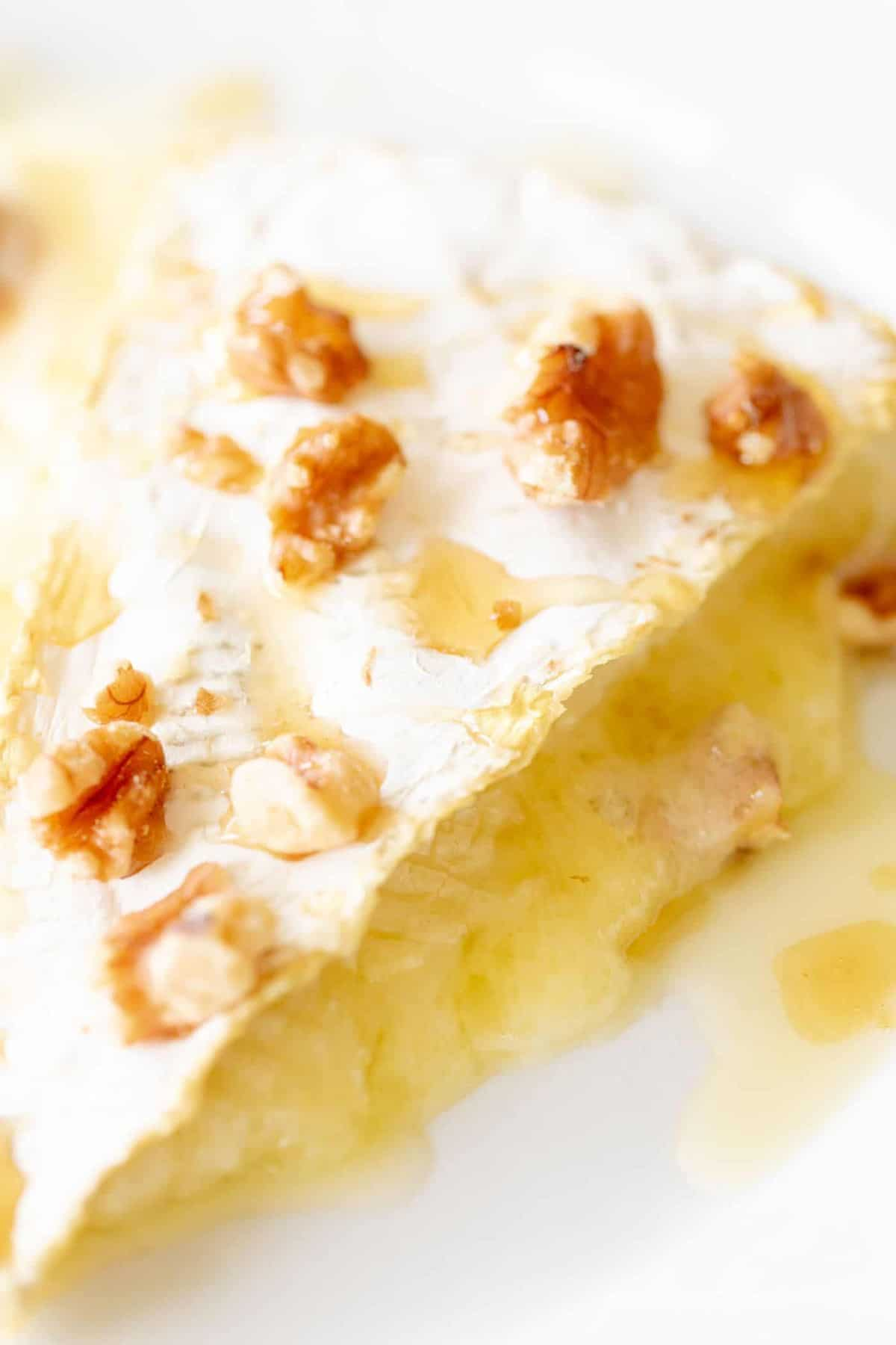 A slice of melted brie covered in honey and pecans.