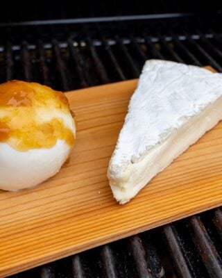 A slice of melted brie and a ball of mozzarella on a cedar plank on a grill..