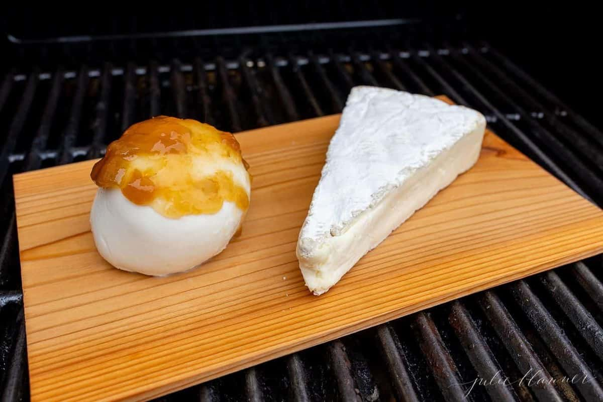 A slice of brie and a ball of mozzarella on a cedar plank on a grill.