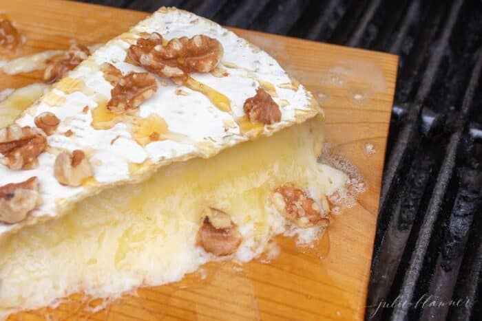 A wedge of melted brie covered in honey and pecans on a cedar plank on a grill..