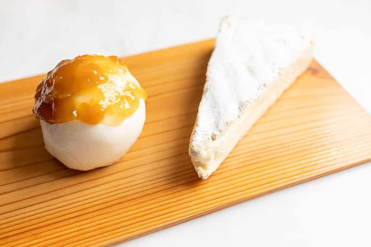 A slice of melted brie and a ball of mozzarella on a cedar plank