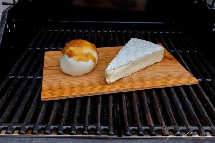 A slice of melted brie covered in honey and pecans on a cedar plank on a grill..
