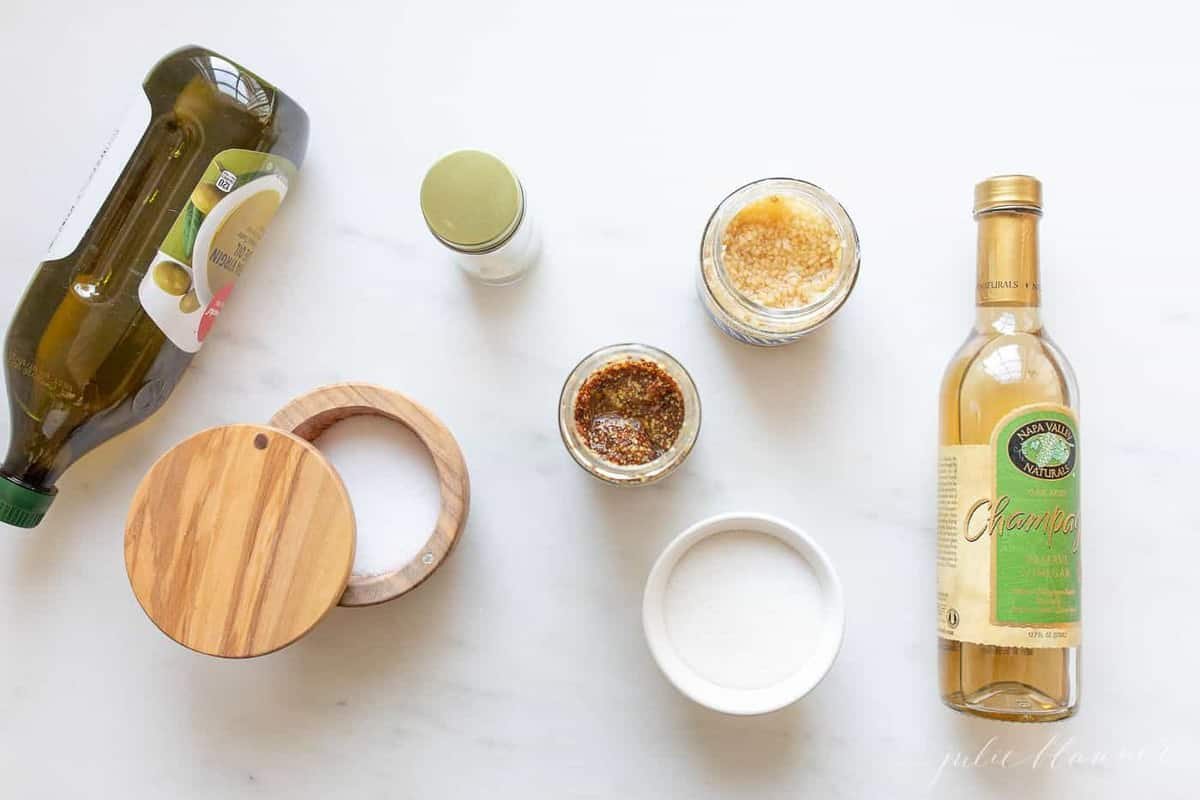 A marble surface with a spread of ingredients to make a homemade vinaigrette recipe.