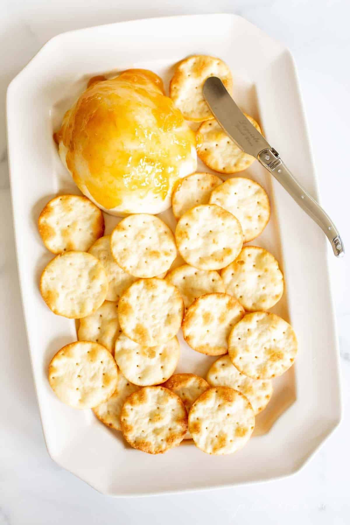 A white platter filled with crackers and a grilled mozzarella appetizer covered in peach preserves.