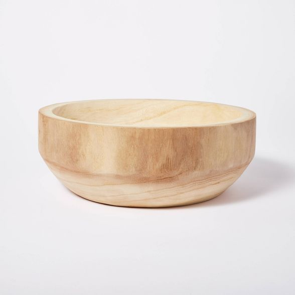 A raw wood bowl on a white surface.