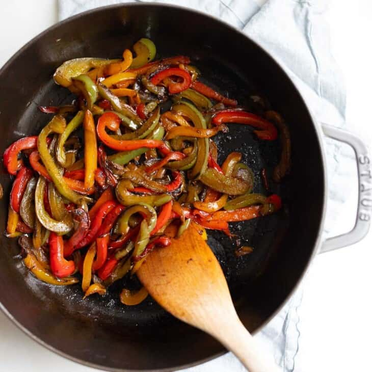 A cast iron pan filled with sauteed peppers, wooden spoon sticking out one side.