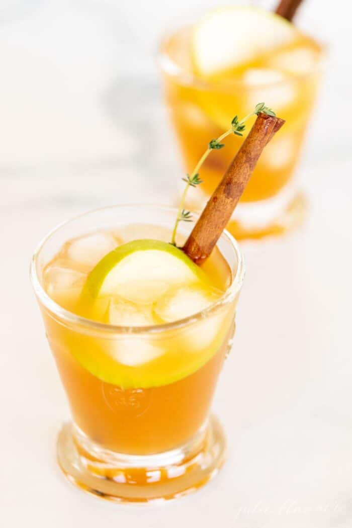 A cocktail glass filled with an apple cider cocktail on ice, garnished with thyme, cinnamon stick and apple slice.