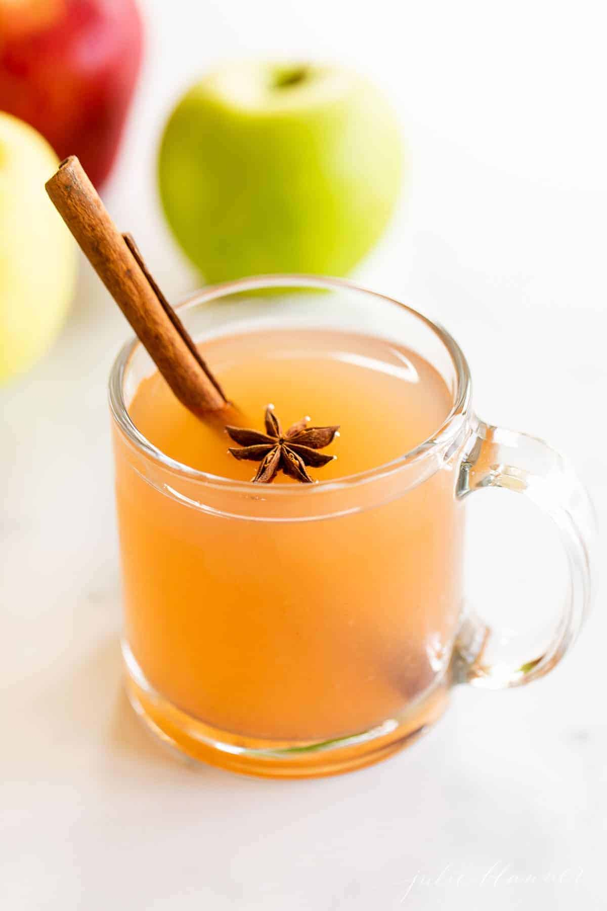 A marble surface with clear mugs full of homemade apple cider, whole apples to the side.