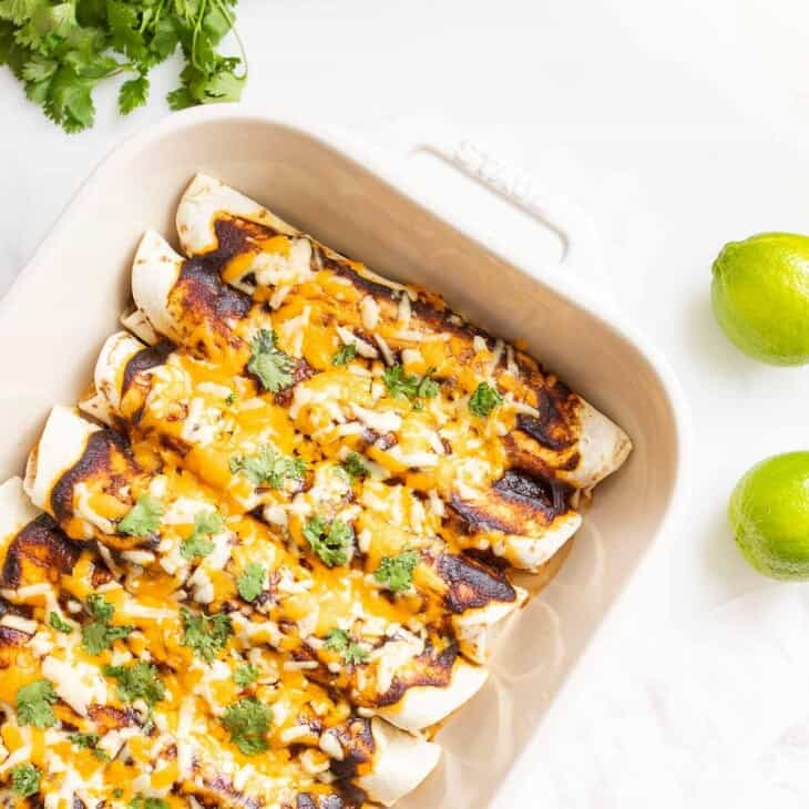 A white baking dish filled with ground beef enchiladas, limes to the side.