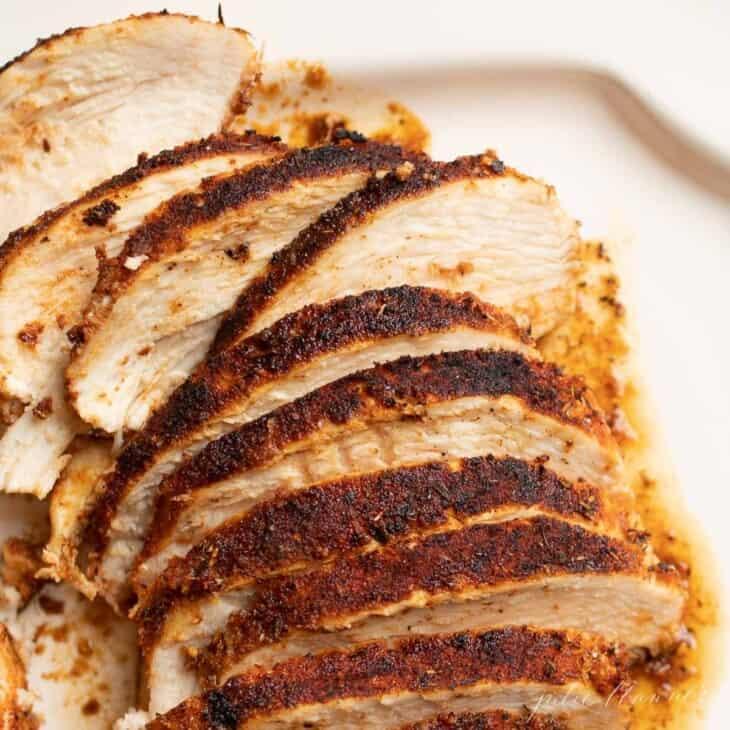 A platter full of sliced blackened chicken.
