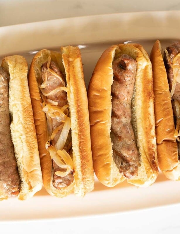 A white tray filled with bratwurst sausages in buns.