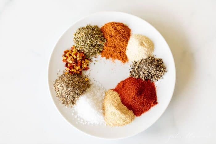 A white plate with piles of spices to make cajun seasoning.