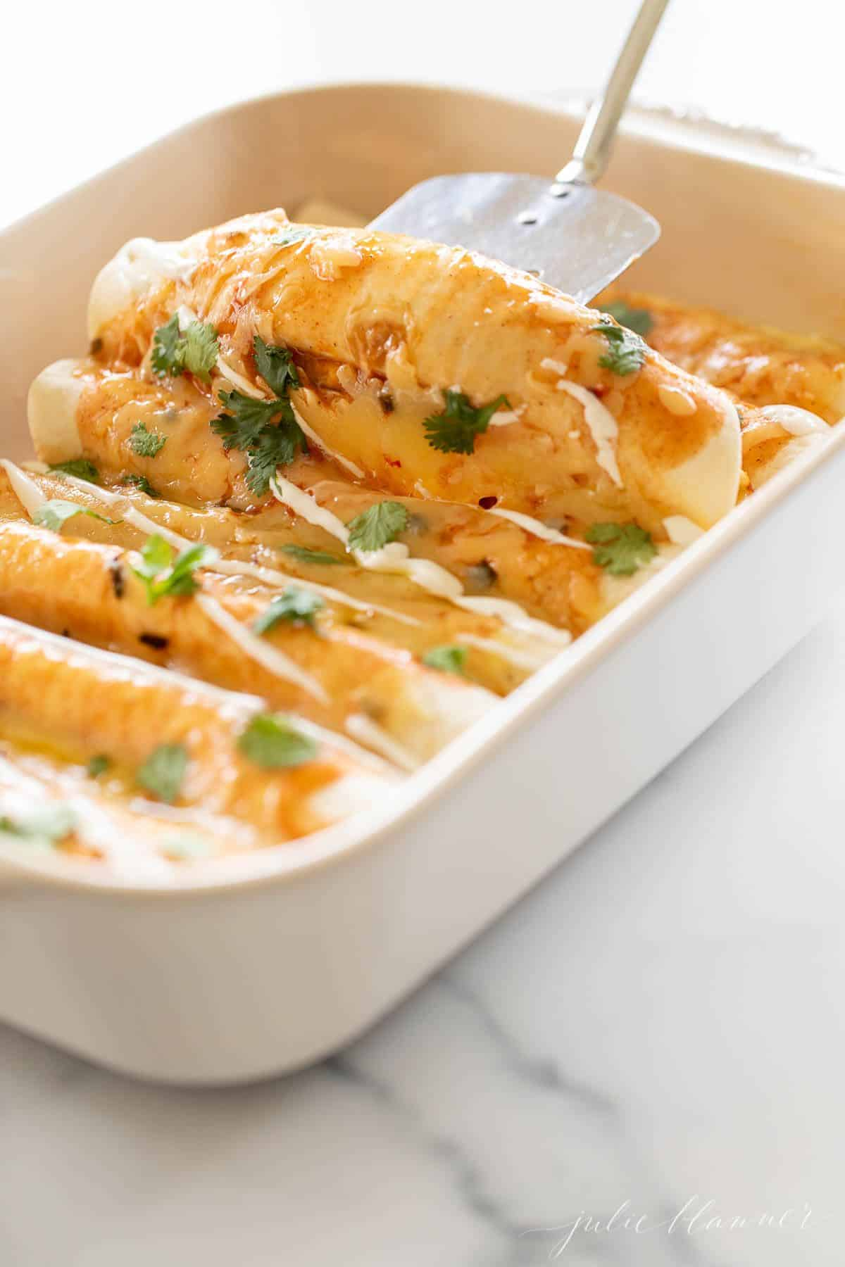 A white casserole dish filled with a cheese enchilada recipe.