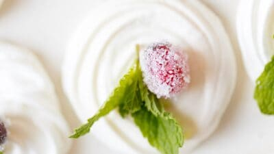 A white merengue christmas cookie with a touch of mint and a sugared cranberry.
