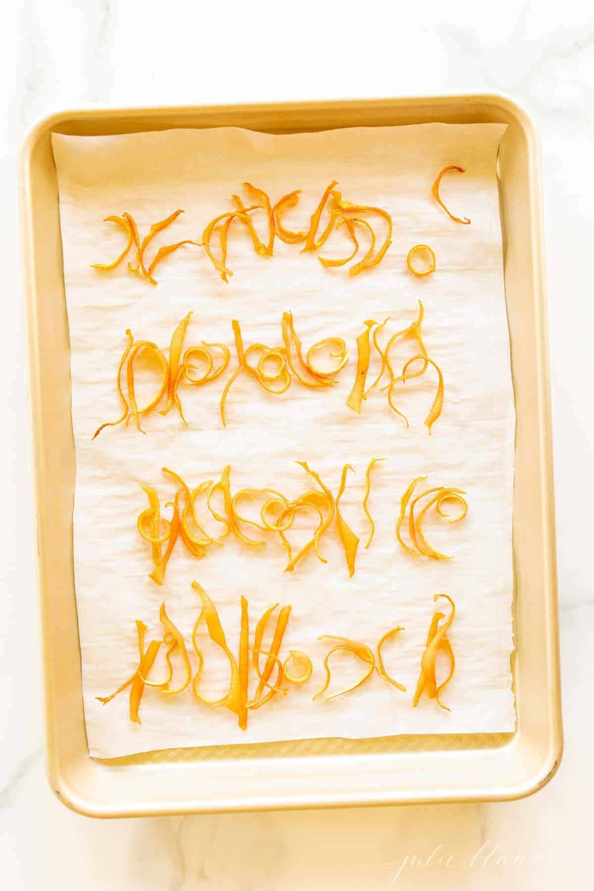 A gold sheet pan lined with parchment paper and covered in dried orange peels.