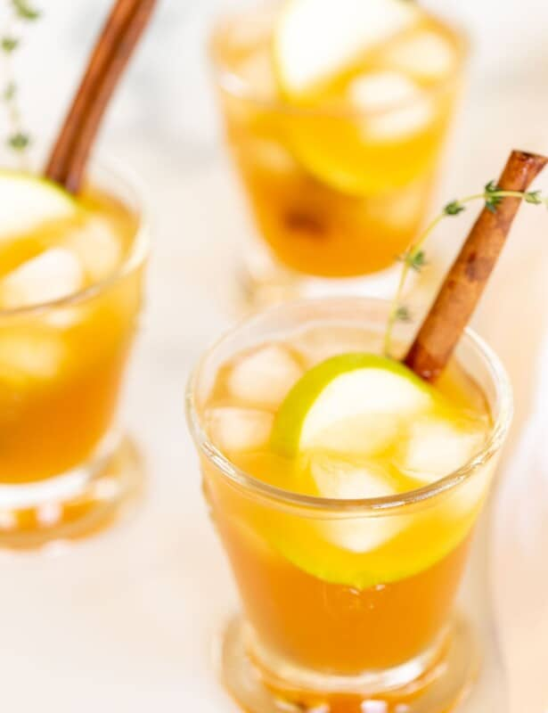 Cocktail glasses filled with an apple cider cocktail on ice, garnished with thyme, cinnamon stick and apple slice.