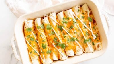 A white casserole dish filled with a chicken enchilada recipe.