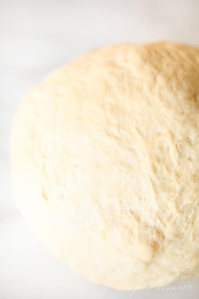 A big slab of dough for easy dinner rolls on a marble surface.