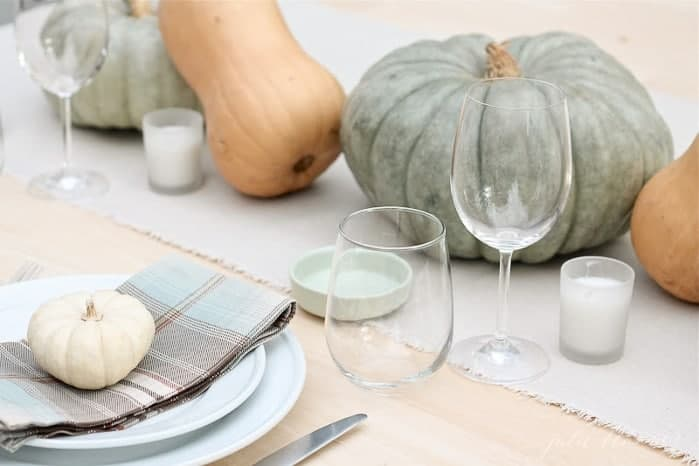A fall centerpiece of pumpkins and gourds with a table set with plaid napkins.