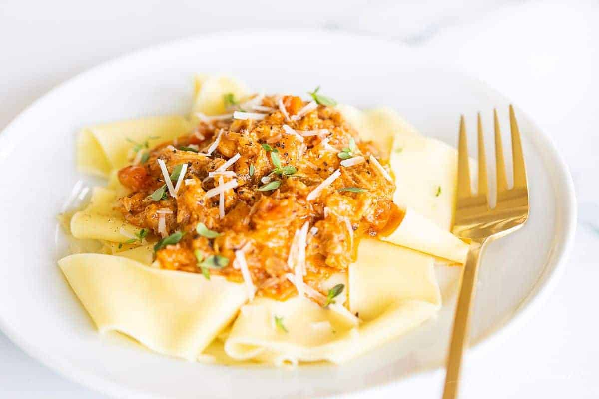 A round white plate on a marble surface featuring pork ragu pasta, gold fork to the side.